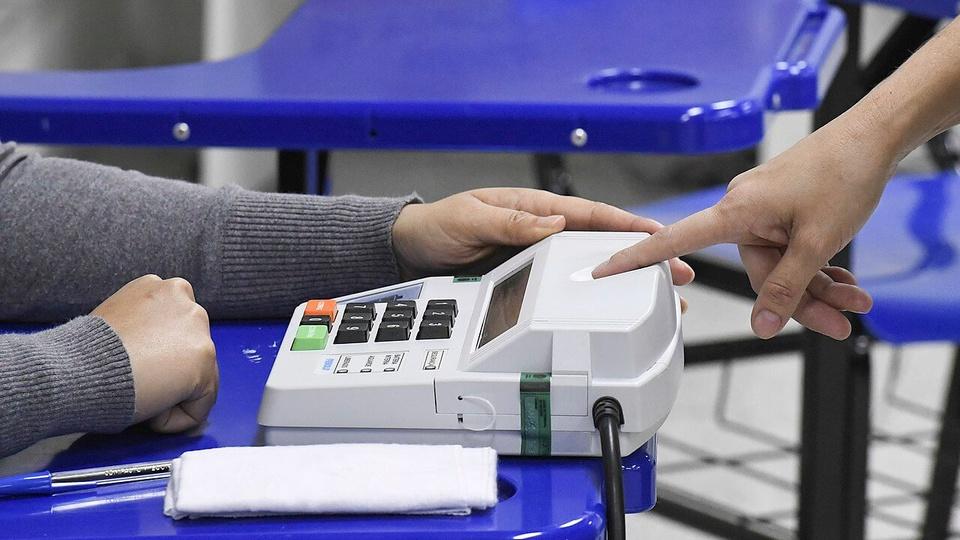TSE veta biometria: pessoa com dedo na máquina de biometria