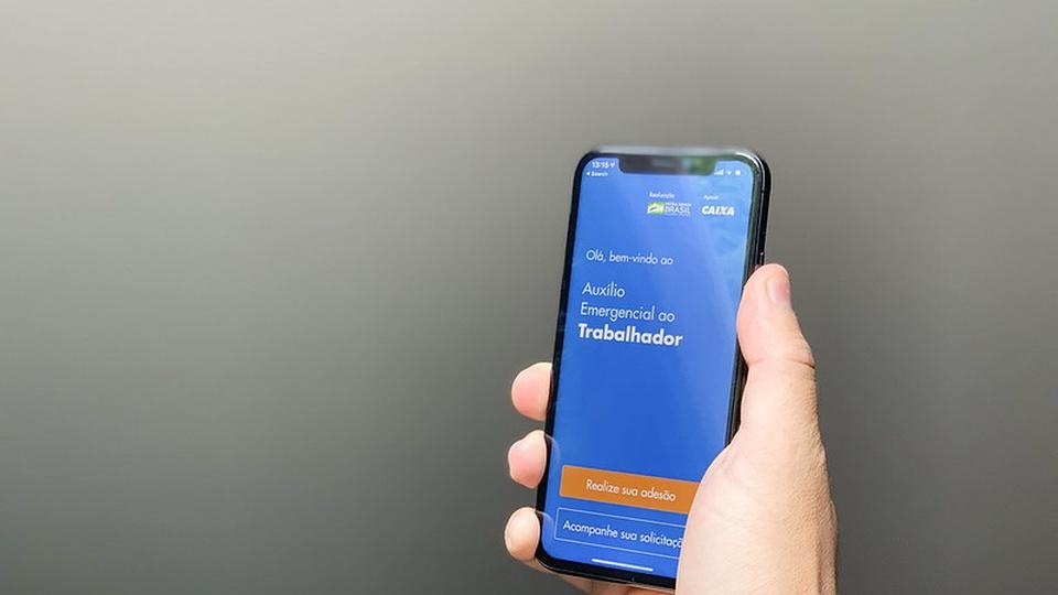 auxílio emergencial 2021: a imagem mostra mão segurando celular aberto na plataforma do auxílio emergencial