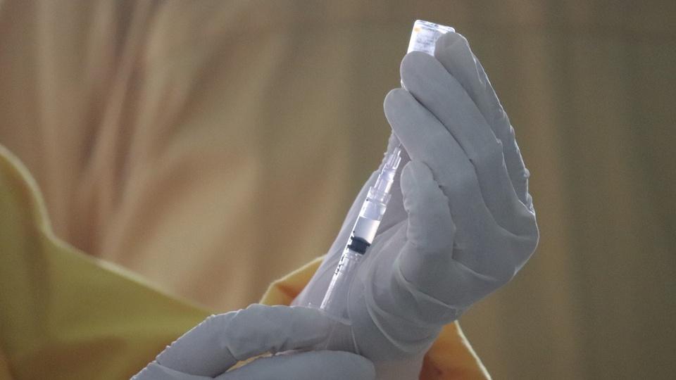 Calendário de vacinação contra a gripe: enquadramento em mão colocando dose de vacina em seringa