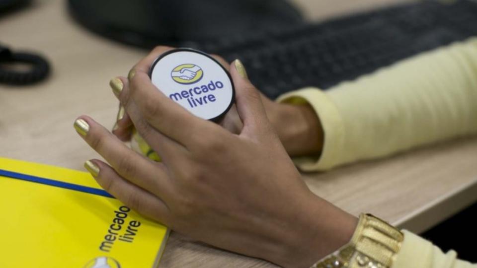 Vagas de emprego Mercado Livre: enquadramento fechado em mãos de mulher manuseando brindes com a logomarca do mercado livre
