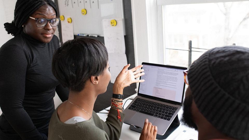 vagas de emprego na BRF: a imagem mostra uma mulher na frente do computador explicando algo para outras duas pessoas