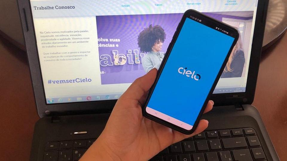 Vagas de emprego na Cielo: mão segurando celular aberto no app da Cielo na frente de computador aberto no site da cielo