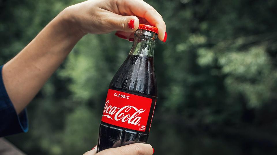 Vagas de emprego na Coca-Cola: pessoa segurando garrafa de vidro da coca-cola