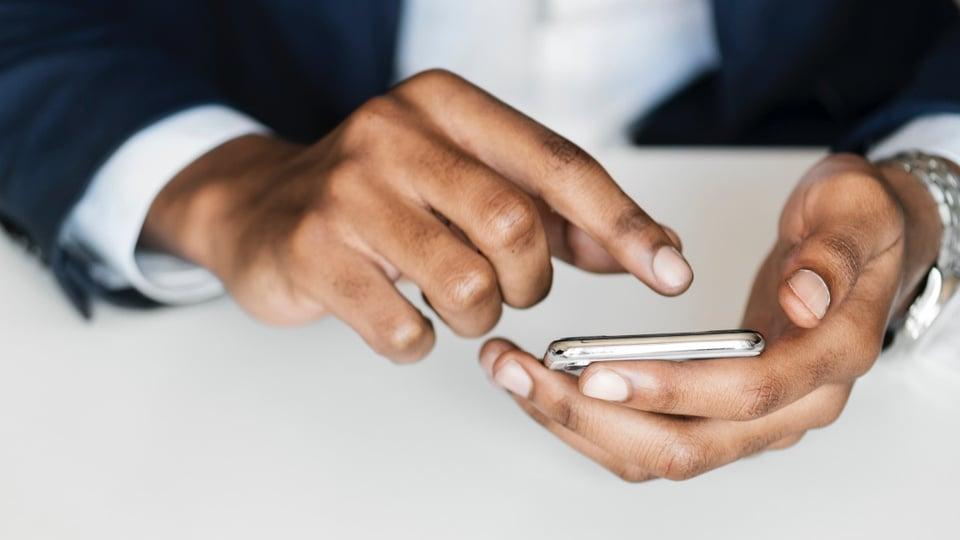 Vagas de emprego na Gi Group: enquadramento fechado em mão mexendo em celular