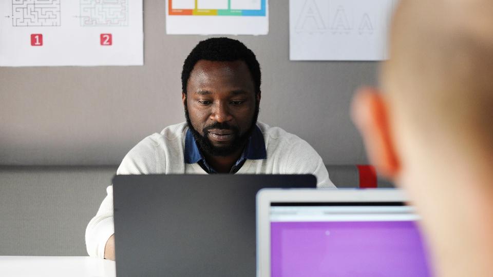Vagas de emprego no Carrefour: enquadramento em homem, sentado, mexendo em notebook