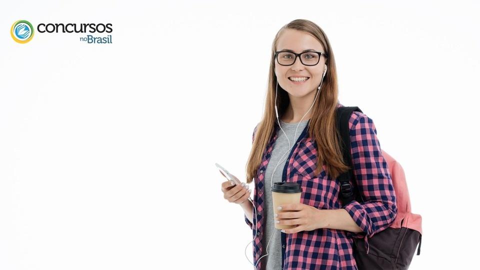 Prefeitura de Sapiranga: estudante mulher, com óculos, usando fone de ouvido, com um copo descartável de café em uma mão e o celular em outra, sorridente