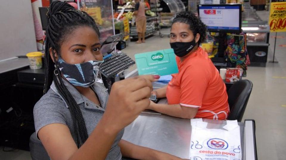 vale-alimentação estudantil: a imagem mostra mulher segurando o cartão do vale-alimentação em frente a caixa de supermercado