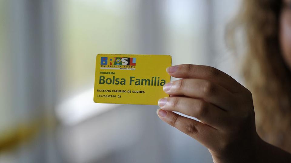 Aumento no valor do Bolsa Família: mão segurando cartão do Bolsa Família