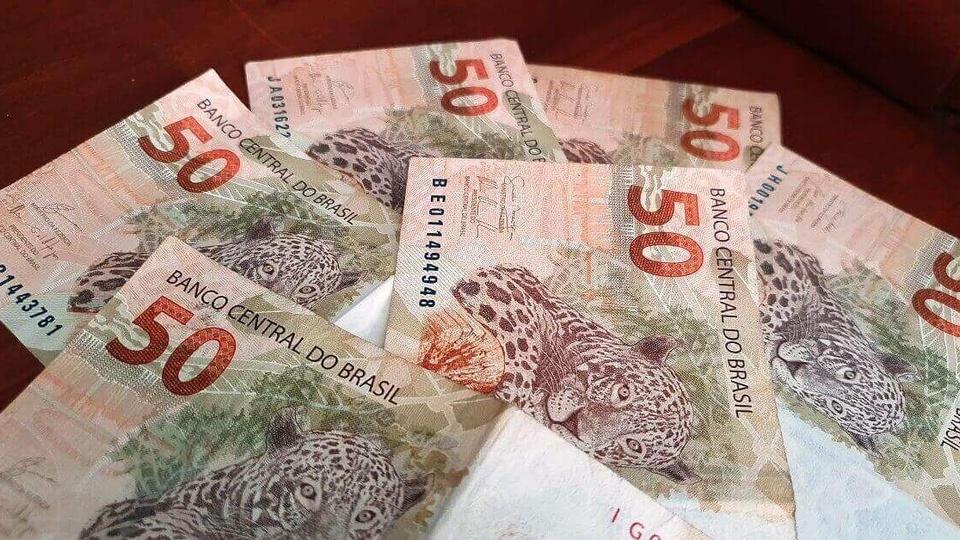 Governo quer salário mínimo no valor de R$ 1.067 para 2021: notas de cinquenta espalhadas em superfície plana