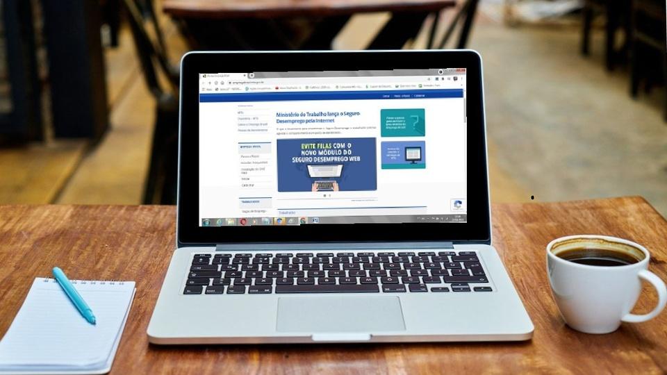 portal emprega brasil: a imagem mostra computador aberto com bloco de anotações do lado esquerdo e xícara de café do lado direito